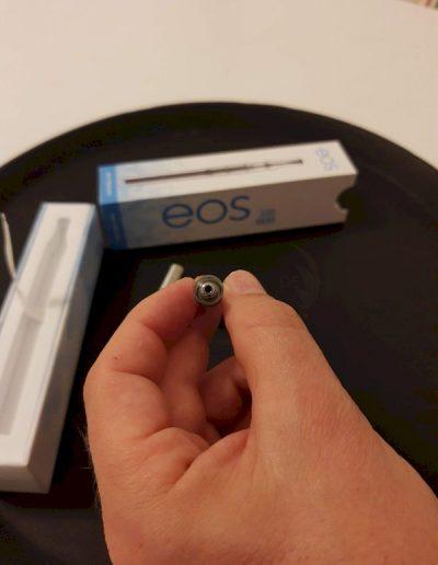 EOS VAPE PEN in linker Hand von oben mit offener e-Liquid Verbrennkammer