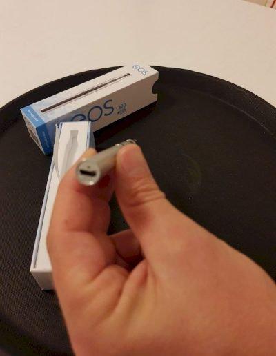 EOS VAPE PEN in linker Hand zeigt USB Stromanschluß zum Aufladen des Pens